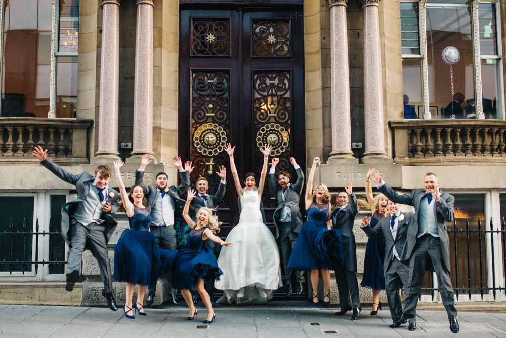 The bride, groom and their bridemaids and groomsmen group shot, jumping.