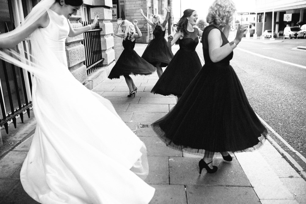 Bride and her maids twirling in their dresses on the street outside the venue.