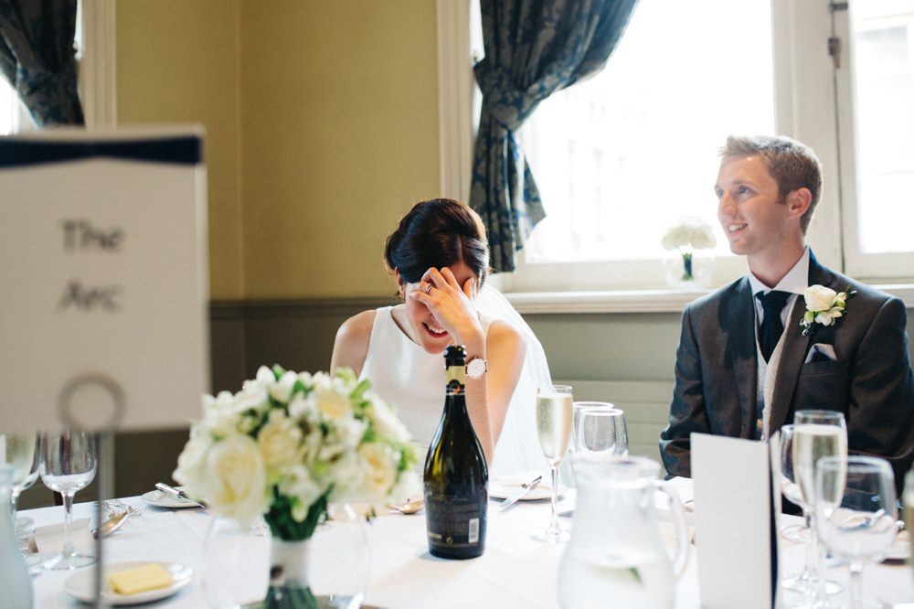 Speeches - bride holds head laughing.