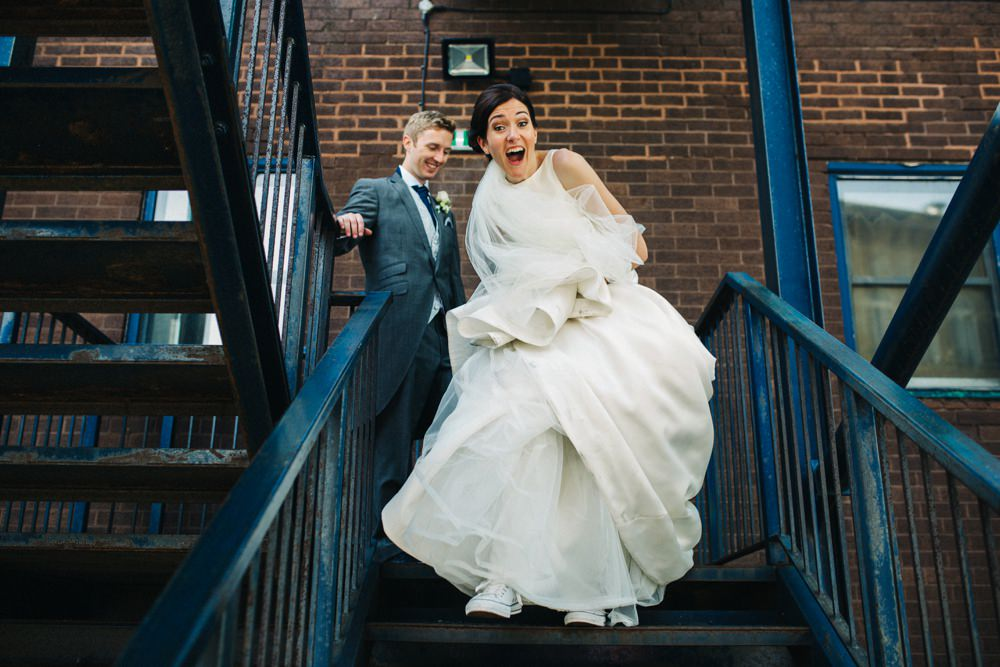 Bride and groom laughing and running down fire escape.