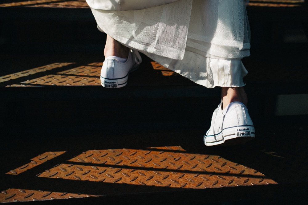 Close up of bride in her converse trainers on fire escape.