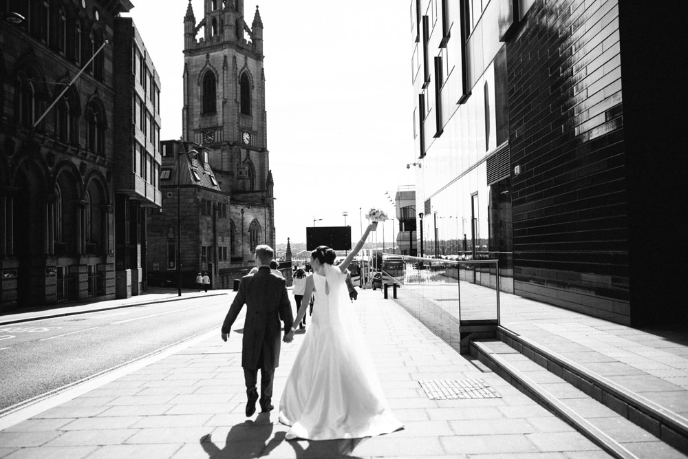 Bride and groom walk along street towards the docks.
