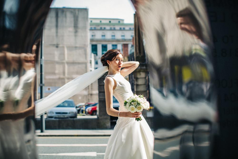 Bride posing and holding on to her veil as she walks through the street.