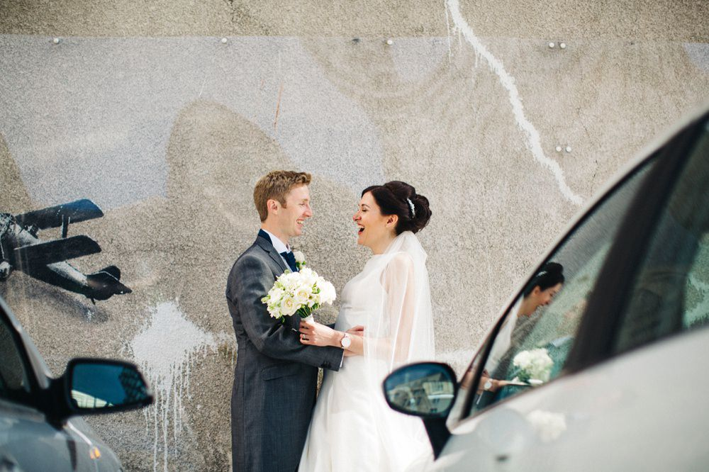 Close up image of couple next to the Banksy.