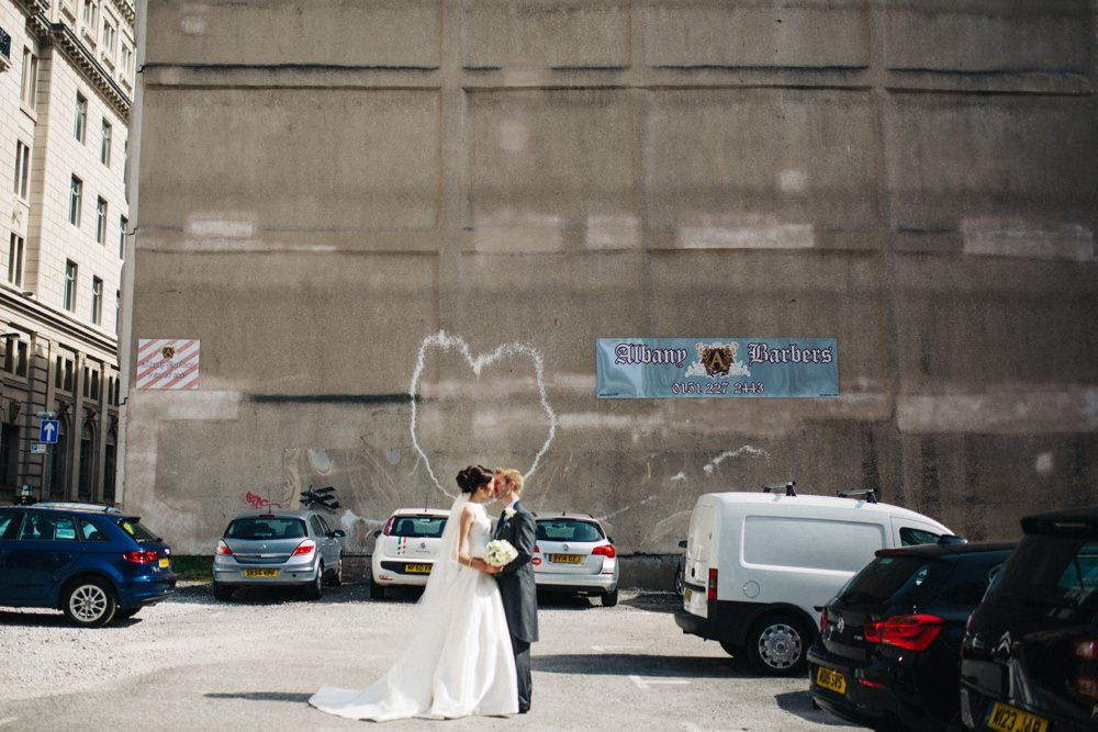The couple kiss with Banksy heart graffitti in the background.
