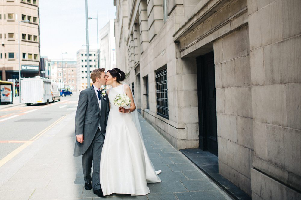 Bride and groom walk through liverpool street in the sunlight.