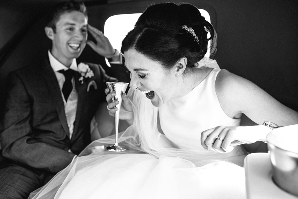 Couple laughing out loud in the wedding car on way to reception.