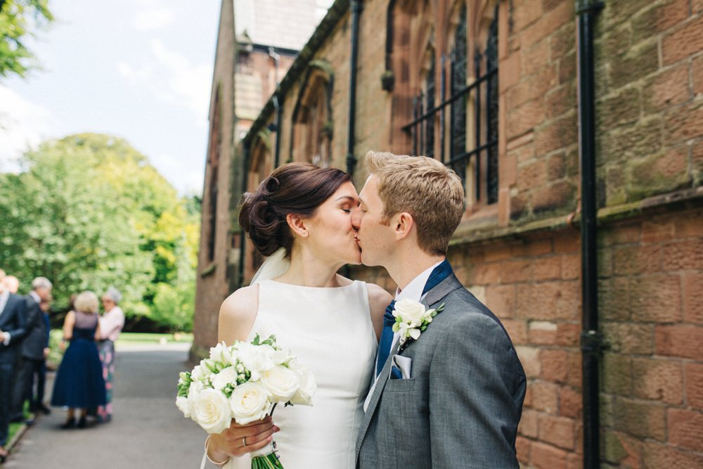 couple kiss outside the church.