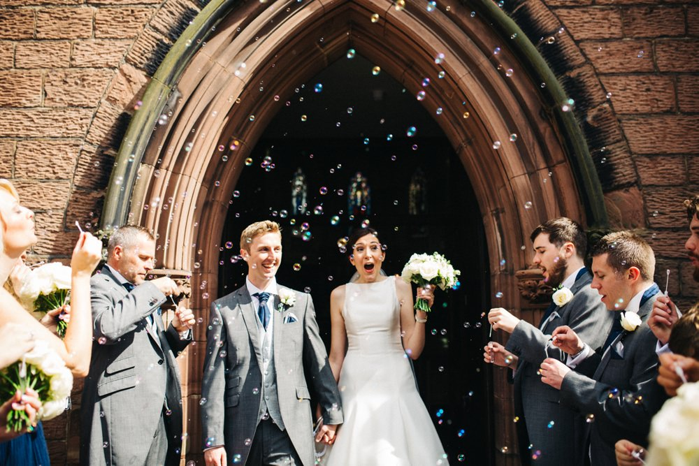 The happy couple after the wedding at the entrance to the church with sunlight and bubble confetti