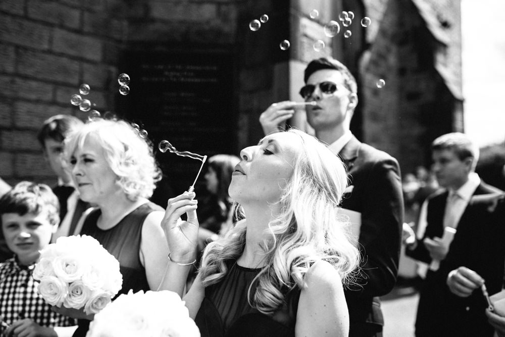 Wedding guests blowing bubbles.