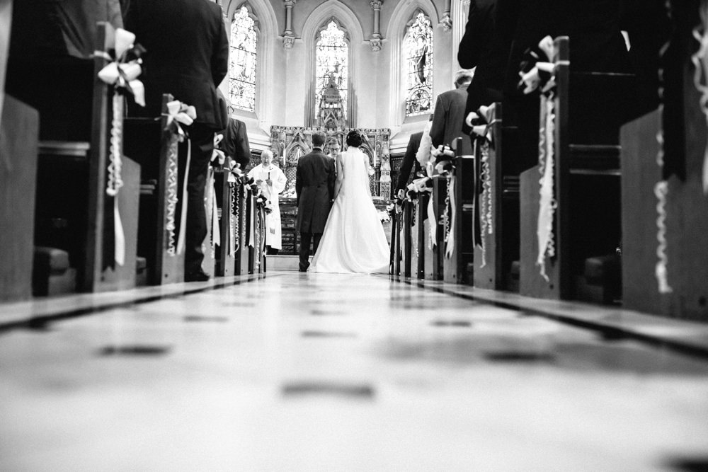 View of Bride and Groom from the back stood at the alter with church pews either side.