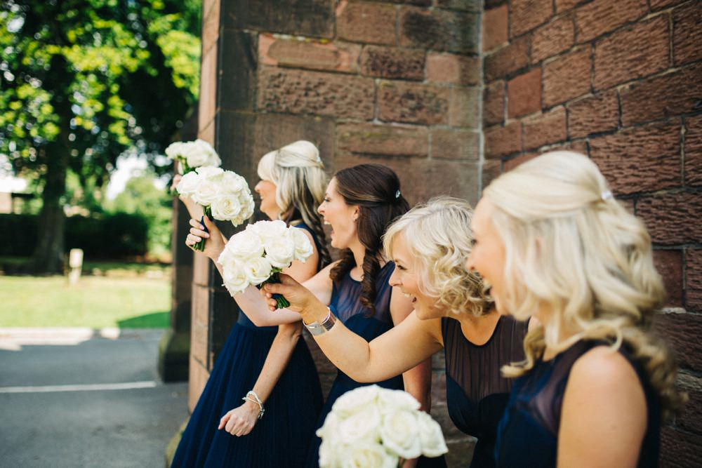 The bridesmaids waiting outside the church, laughing and cheering the brides arrival.