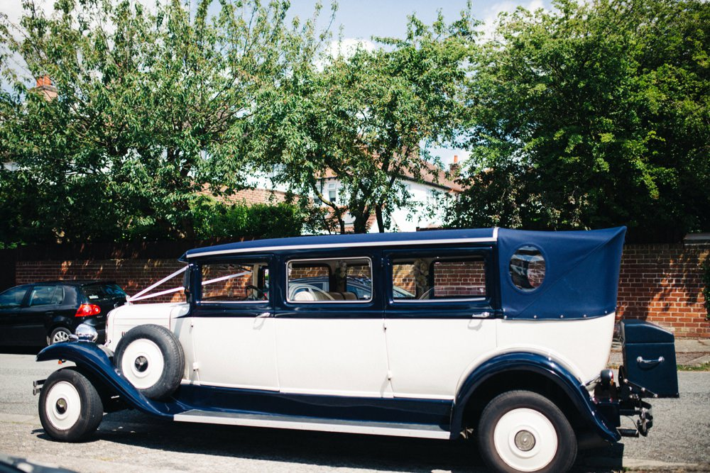 Their beautiful vintage transport, a navy and cream car.