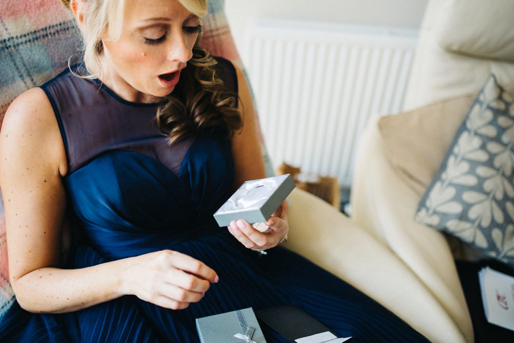 Bridesmaid reacts with a gasp at lovely gift....a bracelet.