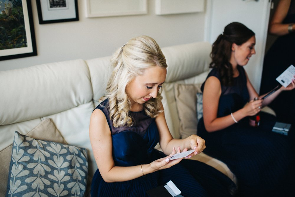 Bridesmaids sat on sofa opening gift.