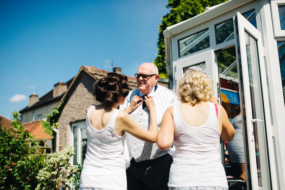 Bride fussing over dad's tie in their garden while getting ready.
