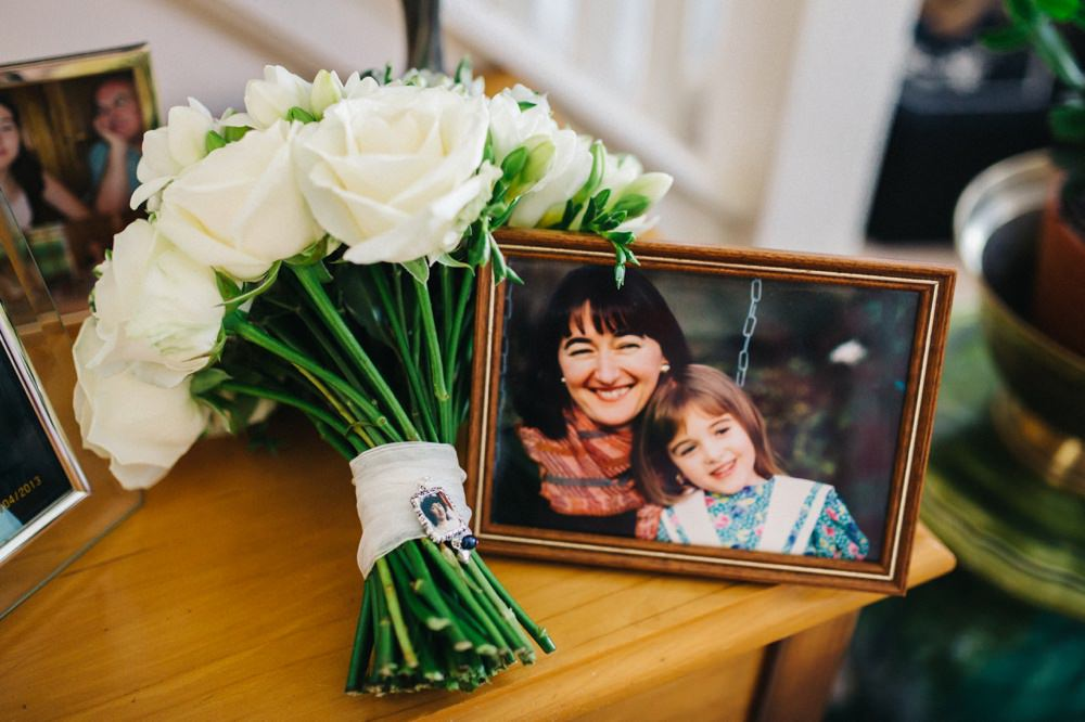 Picture fram of bride as little girl with her mum next to her bouquet