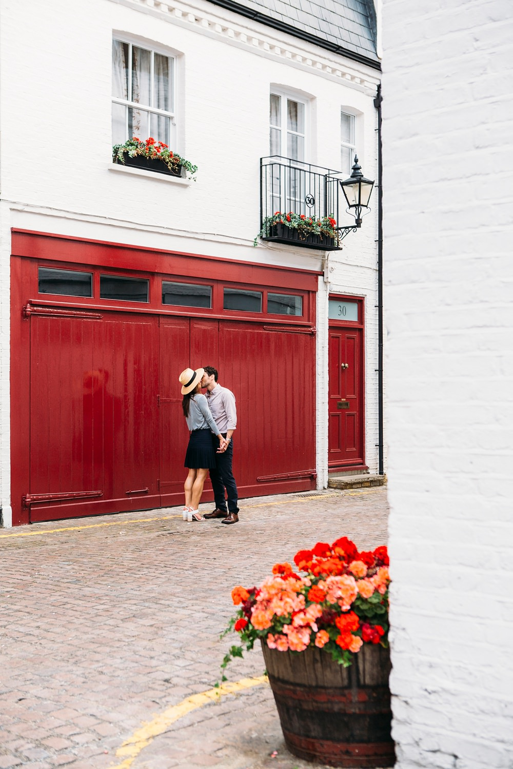 couple stood outside red garage doors