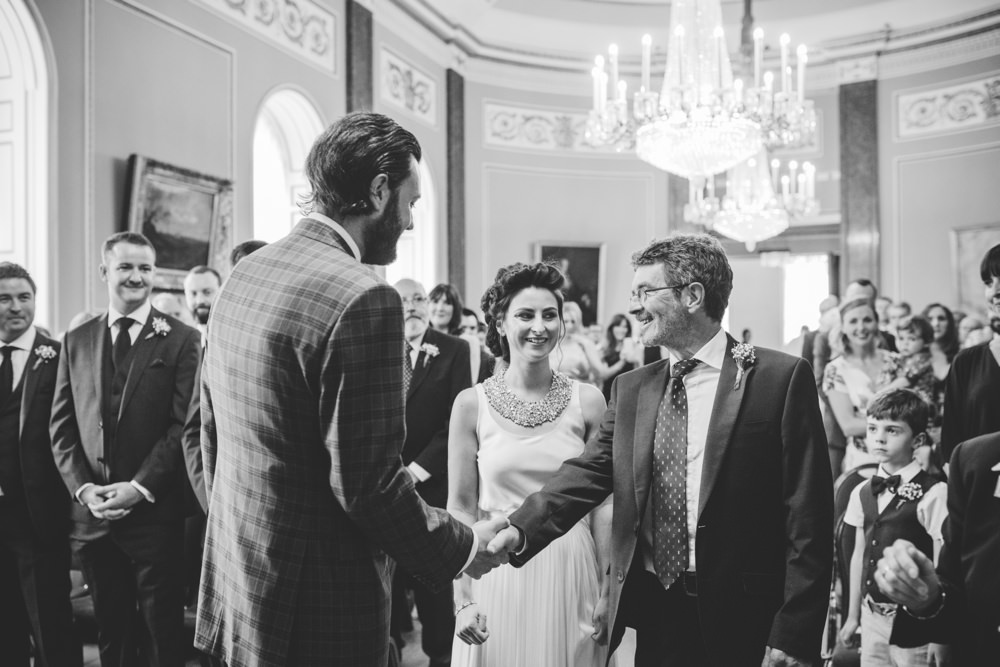 groom greets father of bride at alter