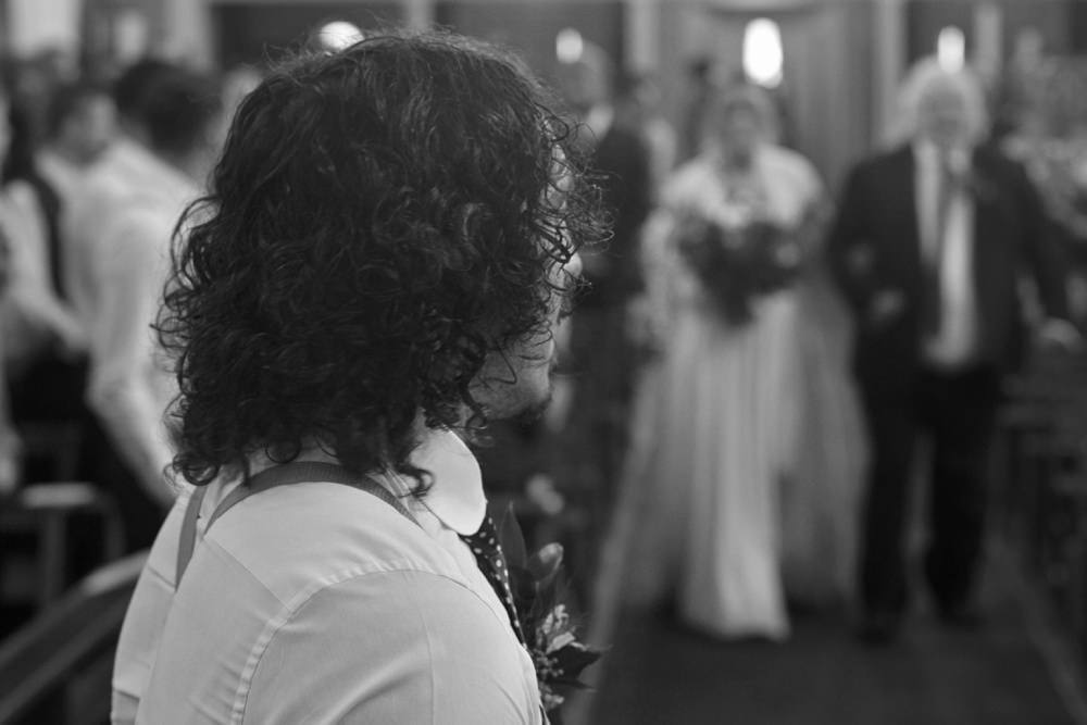 groom waiting for bride as she walks down the aisle