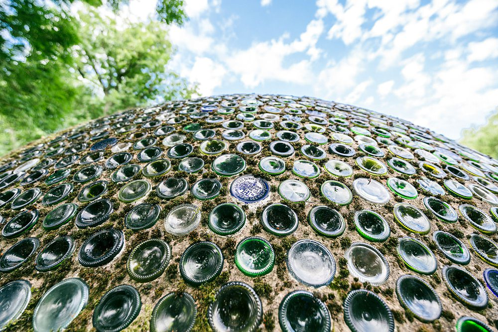 glass bottle house in grounds of water garden
