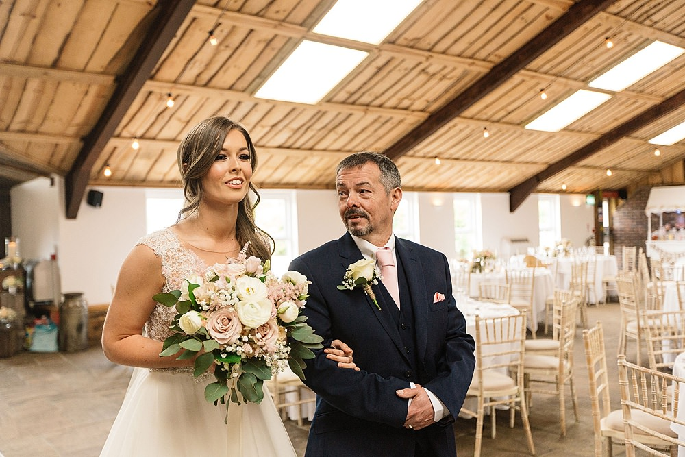 bride and dad arrive at rustic venue