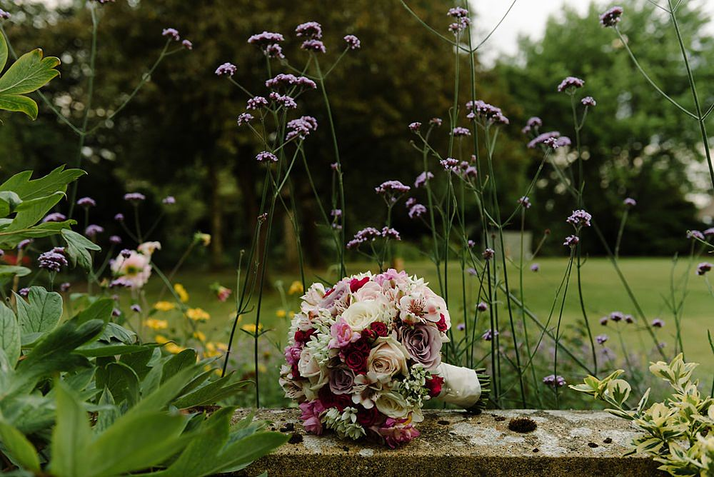 The brides pretty summer bridal bouquet sat on a wall in the garden